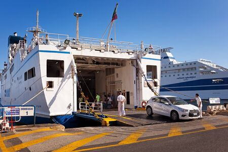 reversing: Naples, Italy - August 10, 2016: At the pier in the port of Naples, a man in the car makes reversing to board the ferry to the island of Ischia, in the maneuver helped by the crew. Editorial