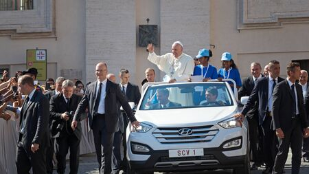 Mother Teresa: Vatican State - September 3, 2016: Pope Francis on the new convertible car, waving to the crowd of faithful gathered in St. Peters Square for the sanctification of Mother Teresa of Calcutta. The cars margins men guarding the security that everything is