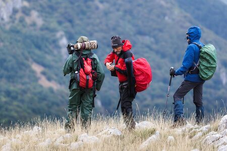 Abruzzo, Italy - September 18, 2016: Three hikers in search of subjects to photograph, on the mountain peaks in the National Park of Abruzzo, Lazio and Molise. Editorial