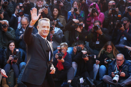 Rome, Italy - October 13, 2016: Tom Hanks on the red carpet at the 11th film festival in Rome, greets the audience.American actor Tom Hanks on the red carpet at the 11th Film Festival in Rome, Hank greets the audience, raising His arm, and behind him a cr