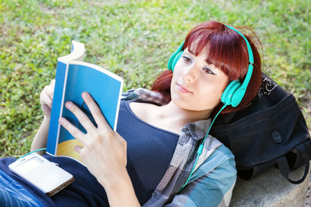 Girl lying on the bench, law book and listening to music on headphones.