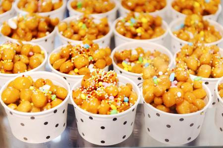 カップは、典型的なナポリのペストリー生地 (小麦粉、卵、ラード、砂糖、アニス リキュールと紙の上を実現) の多くの小さなボールで構成される主