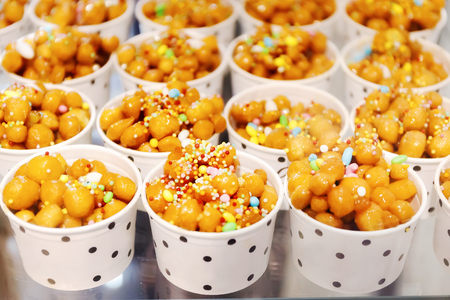 Cups filled with Struffoli, typical Neapolitan pastry consisting of many small balls of dough (realized on paper with flour, eggs, lard, sugar, anise liqueur), fried in oil and wrapped in warm honey. Decorated with colored sprinkles.