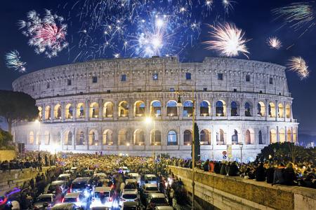 ローマ, イタリア - 2017 年 1 月 1 日: 徒歩や車で花火とシャンパンのボトルと新年の到来を祝うためにコロシアムの前に集まる人々 の群衆。