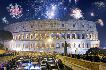 Roma, Italia - 1 de enero de 2017: una multitud de personas a pie y en coche, se reúnen frente al Coliseo para celebrar la llegada del Año Nuevo con fuegos artificiales y botellas de champán.