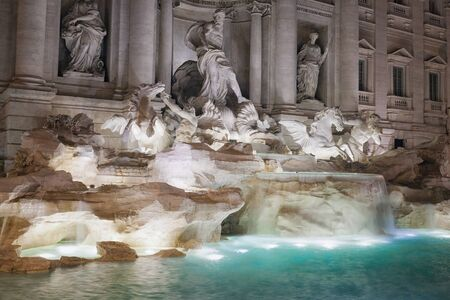 The famous Trevi fountain shooting night in its central part, with the main niche. The long exposure shows the movement of the falls. Trevi fountain is taken laterally, echoing the large tub with water artificially illuminated.