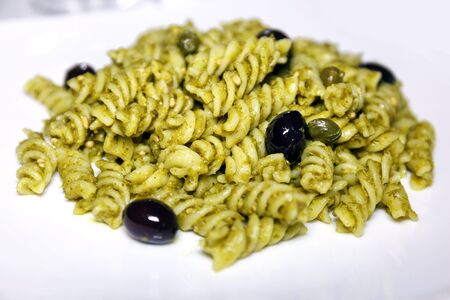 Fusilli topped with pesto sauce, black olives and capers. Meal ready to eat Stock Photo