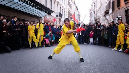 Rome, Italy - January 28, 2017: Celebration of the Chinese New Year in Rome, the year of the rooster. monk athlete in martial arts, he performs with the sword in the street during the procession.