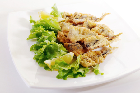 Typical dish of Neapolitan cuisine in Italy. Anchovies breaded in flour, then egg, fried in peanut oil. Ready meal accompanied by a green salad and lemon garnish.