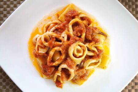 Squid, pasta with tomato sauce and squid cut ring. typical of Neapolitan cuisine dish. Stock Photo
