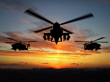 Silhouette of three military helicopters over sunset