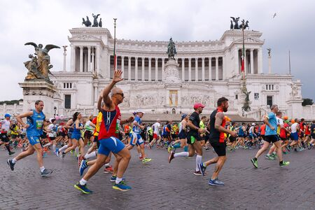 Rome, Italy - April 2, 2017: Athletes participating at the 23rd Rome marathon run through the street circuit passing in front of the altar of the homeland, the monument to Vittorio Emanuele II, king of Italy.