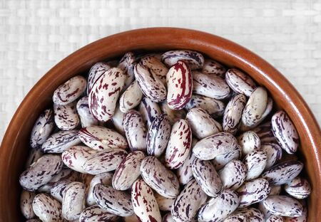 borlotti beans: Bowl full of raw beans, on white background. View from above. Stock Photo