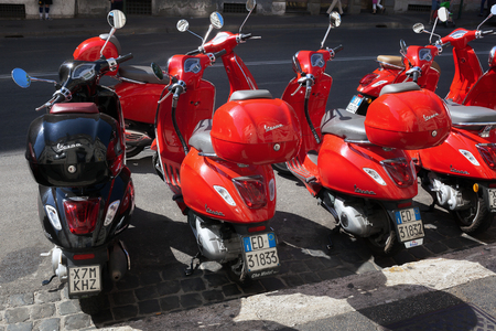 Rome, Italy - June 9, 2017: A row of red Vespa scooters is parked along Via Cavour, where you rent a scooter. Editorial