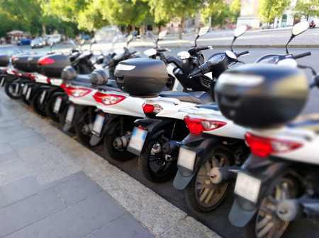 Series of white scooter parked in a row in the city.