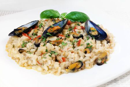 spelled: Dish prepared with mixed cereals, rice, spelled and barley, with mussels. Seasoned with tomato sauce and topinambur.