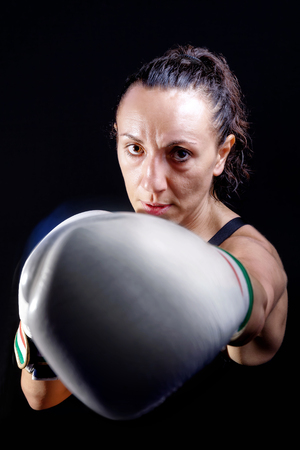 Boxer woman with boxing gloves. Portrait with half bust on black background, artificial lighting.
