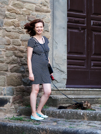 Cortona, Italy - July 15, 2017: Girl strolls through the streets of the small Tuscan town carrying her cat on the leash. Editorial