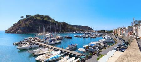 Vista panoramica del piccolo porto di Chiaiolella Marina, con barche turistiche ormeggiate al molo. A sinistra il promontorio di Punta della Palombara. Archivio Fotografico - 86560439