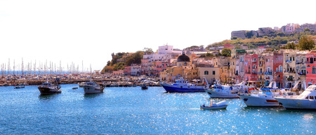 Panoramic view of Procidas marina, with colorful houses overlooking the small harbor and boats moored in the sun.