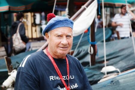Manarola, Riomaggiore (SP), Italy - September 15, 2017: Portrait of an old fisherman, against the background of boats parked at the small harbor.