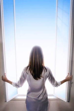 room to let: A woman with long hair and shrugging as she opens the window doors to let the light into the room. Space for text. Stock Photo