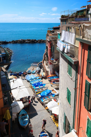 View from the top of the small marina of the village of Riomaggiore, with moored boats and some tourists. Imagens