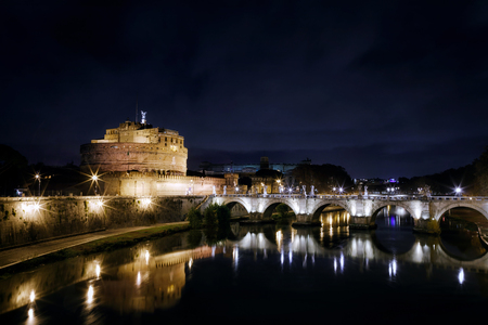 Rome, Italy - December 14, 2017: Night view of Castel Santangelo, mausoleum of Hadrian in Rome, Italy. In the scene is clearly visible the homonymous bridge in front, with its beautiful arches of white marble, under which flows the river Tiber. The sky i