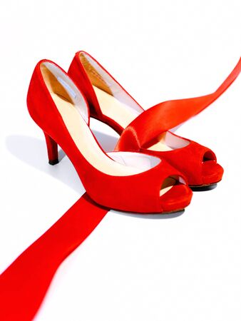 Red shoes women, on a white floor and are joined by a red ribbon, which is the common thread that unites them: violence against women, symbolized by red shoes.