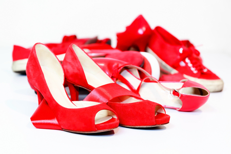 Red shoes women of various models, are based on a white floor and are joined by a red ribbon, which is the common thread that unites them: violence against women, symbolized by red shoes. Stock Photo