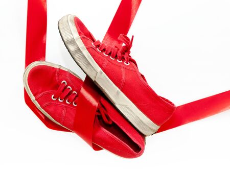 The model of red shoes for women, casual shoes on a white floor and joined by a red ribbon, which is the common thread that unites them: violence against women, symbolized by red shoes. Stock Photo