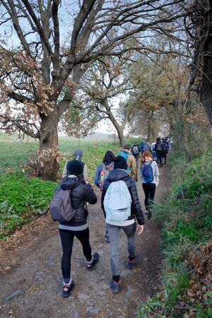 Castel Giuliano (RM), Italy - January 21, 2018: Group of numerous hikers crosses a path in the countryside, following the path. Editorial