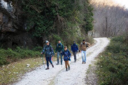 Trevi nel Lazio (FR), Italy - January 28, 2018: Group of hikers crosses a path in the countryside, following the path.