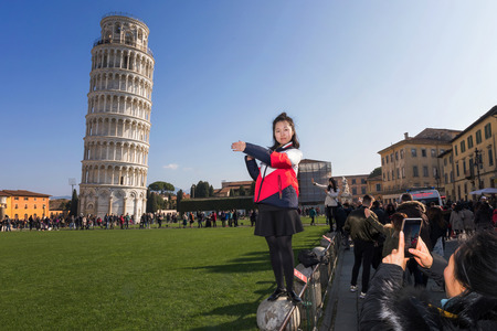 Pisa, Italy - February 11, 2018: Asian girl poses for a picture with the famous Tower of Pisa in the background, in Piazza dei Miracoli crowded with tourists.