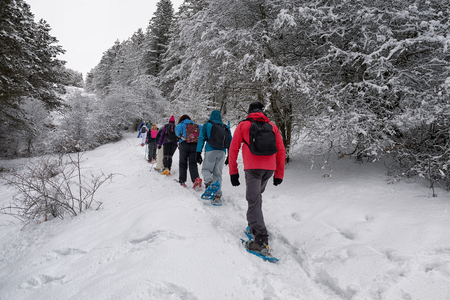 Subiaco, Italy - February 25, 2018: In the middle of winter, group of people take an excursion on the snow-covered mountain, wearing snowshoes on their feet to avoid sinking in the fresh snow, with th 報道画像