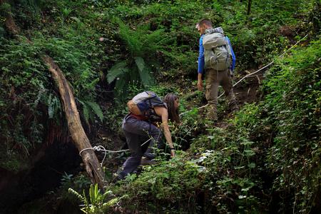 カルカタ(VT)、イタリア - 2018年4月25日:森の中で2人のハイカーがロープの助けを借りて上り坂の道を登ります。彼らはシダ、苔、倒れた木の幹の豊かな静脈に囲まれています。