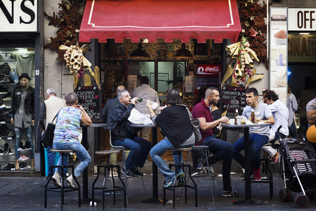 Naples, Italy - October 15, 2017: Group of people sitting at tables in the street, eating and talking to each other, in the city center. In the background a typical restaurant that distributes street food.