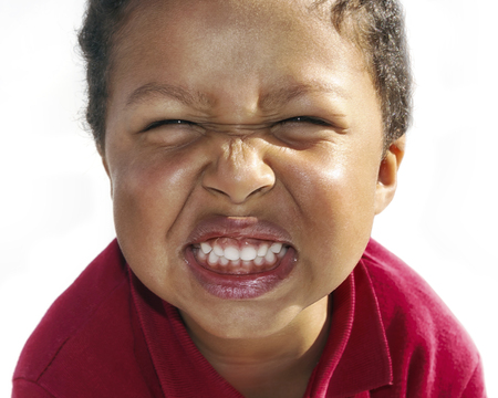 Face of child grimacing. Grind your teeth, smile with your eyes. Red t-shirt, white background.