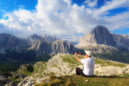 Immersed in the beautiful alpine scenery, a man takes a picture with his cell phone to the high-altitude landscape with the mountain peaks and the cloudy sky.