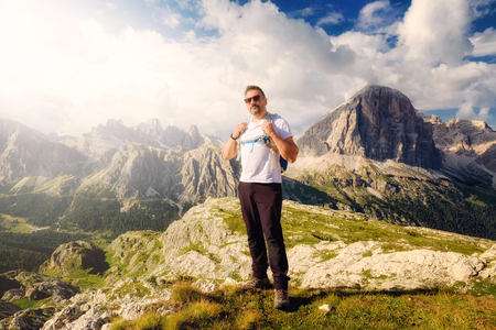 A hiker on the top of the Dolomites. In the background the mountain landscape of the Alpine peaks at sunset. Archivio Fotografico - 108818441