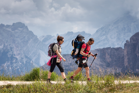 Cortina d'Ampezzo, Italy - August 18, 2018: A family of hikers walks on the mountain path, the father carries his son on his shoulders. In the background, the peaks of the dolomites. Stock Photo - 108791867