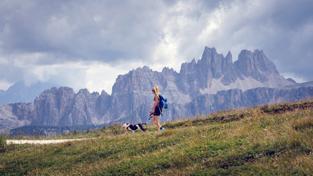 Cortina d'Ampezzo, Italy - August 18, 2018: a hiker and his dog walk on the mountain path on a cloudy summer day. In the background, the peaks of the dolomites (Croda da Lago).