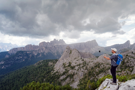 Man takes pictures with his cell phone to the mountain landscape of the Alpine peaks. Foto de archivo