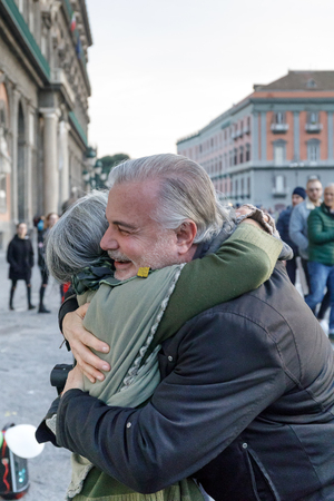 Naples, Italy - December 16th 2018: Piazza del Plebiscito, a hug between two people on the street in a sign of solidarity and peace. We are in the Christmas period.