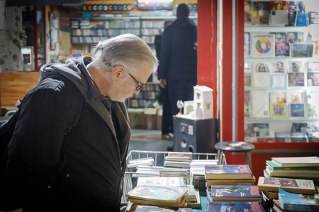 Naples, Italy - December 16, 2018: A man observes a street stall with comics, books and music CDs for sale. 報道画像
