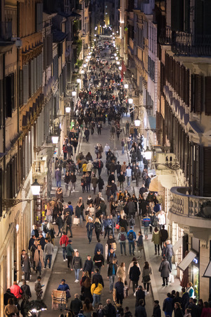 Rome, Italy - 10 March 2019: Crowd in Via Condotti, night shots with many people. At the edge of the street the high fashion shops of the capital.