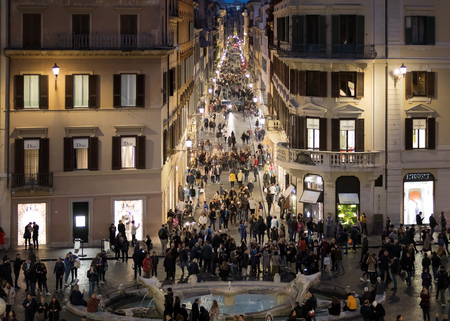 Rome, Italy - 10 March 2019: Crowd in Piazza di Spagna, night shots with many people. At the center of the famous Barcaccia fountain, in the background Via Condotti. Фото со стока - 122153022