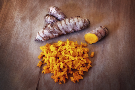Turmeric, tuber, intact and broken root. Single ingredient isolated on wood background.