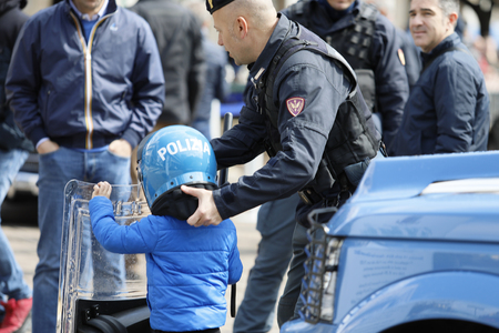 Rome, Italy - April 14, 2019: Piazza San Giovanni Bosco, a policeman in the mobile operating department helps a child to wear his helmet, during the event to celebrate the 167th anniversary of the Italian Police. Standard-Bild - 122153303