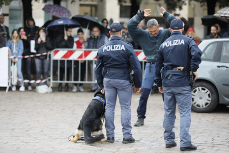 Rome, Italy - April 14, 2019: Piazza San Giovanni Bosco, dogs from the canine department simulate an arrest, during a practical exercise with dogs, in front of the public in the square. Standard-Bild - 122153359